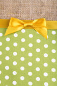 Sackcloth with color ribbon and bow on color fabric background — Stock Photo