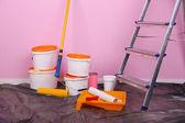 用油漆和梯放在背景墙上的水桶。概念的修复工程在房间里的照片 — 图库照片