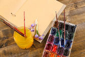 Composition with colorful watercolors, brushes and sketcher on wooden background  — Stock Photo