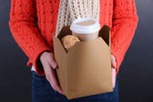 Woman holds box with coffee and cookies on black background — Stock Photo