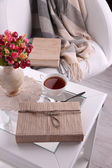 Composition with cup of hot drink and cookies on wooden table near armchair — Stock Photo