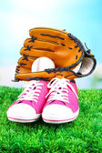 Beautiful gumshoes and baseball ball, glove on green grass, on bright background — Stock Photo