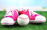 Beautiful gumshoes and baseball ball on green grass, on bright background — Stock Photo
