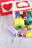 Bags with bobbins of colorful thread and woolen balls on wooden background — Stock Photo