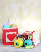 Bags with bobbins of colorful thread and woolen balls on wooden table, on light background — Stock Photo