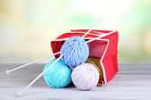 Woolen balls of yarn in rustic craft bag, om wooden table, on light background — Stock Photo