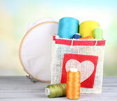 Colorful bobbins of thread  in bag, on wooden table, on light background — Stock Photo