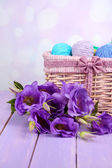 Purple artificial eustoma and woolen balls of yarn in basket on light background — Stock Photo