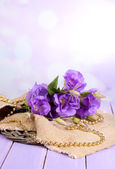 Purple artificial eustoma on sackcloth on color wooden  table, on bright background — Stock Photo
