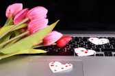Bright hearts and flowers on computer keyboard close up — Stock Photo