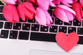 Red heart and flowers on computer keyboard close up — Stock Photo