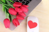 Computer with red heart and flowers on table close up — Foto Stock