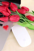 Computer with red heart and flowers on table close up — Stockfoto