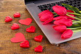 Computer with red hearts and flowers on table close up — Stock Photo