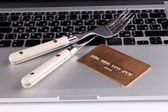 Credit card with fork and knife on computer keyboard close up — Stock Photo