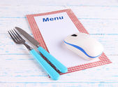 Computer mouse with menu and cutlery on wooden background — Foto Stock