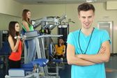 Young trainer and womans engaged in simulator in gym — Stock Photo