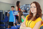 Young trainer and womans engaged in simulator in gym — Foto de Stock