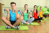 Young beautiful peoples engaged with dumbbells in gym — Stock Photo