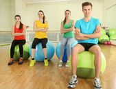 Young beautiful peoples engaged with balls in gym — Stock Photo