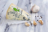 Tasty blue cheese on old wooden table — Stock Photo