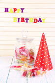 Tasty candies in jar with party hat on table on wooden background — Stock Photo