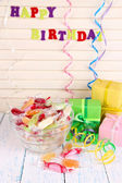 Tasty candies in vase with presents on table on wooden background — Foto Stock