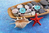 Wooden bowl with Spa stones, sea shells and candles on color background — Stock Photo