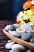 Composition with  spa stones and candles in wooden bowl, near flowers on bright background — Stock Photo