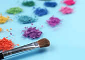 Rainbow crushed eyeshadow and professional make-up brush on blue background — Stock Photo