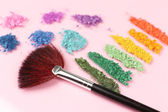 Rainbow crushed eyeshadow and professional make-up brush on pink background — Stock Photo