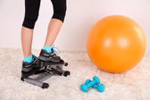 Young beautiful fitness girl exercising on stepper in gym — Stock Photo