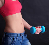 Young beautiful fitness girl exercising with dumbbells, close-up, isolated on black — Stock Photo