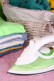Hierro y pila de ropa colorida y canasta en mesa cerrar — Foto de Stock