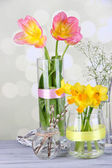 Beautiful spring flowers on old wooden table, on light background — Stock Photo