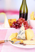 Assorted cheese plate , grape and wine glass on table, on light background — Stock Photo