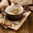 Mushroom soup in pot, on wooden background — Stock Photo