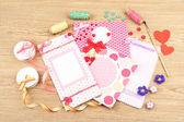 Beautiful hand made post cards and scrapbooking elements, on wooden table — Stock Photo