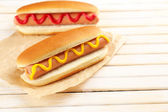 Tasty hot dogs on wooden table — Stock Photo