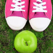 Beautiful gumshoes and apple on green grass background — Stock Photo #42842631
