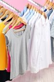 Different clothes on hangers, on pink background — Stock Photo