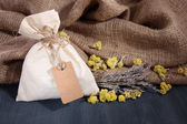 Textile sachet pouch with dried flowers, herbs on wooden table, on sackcloth background — Stock Photo