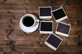 Coffee cup and old blank photos, on wooden background — Stock Photo