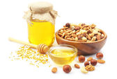 Sweet honey and different nuts, isolated on white — Stock Photo