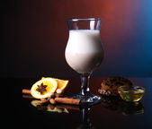Eggnog with spices and orange on colorful background — Stock Photo