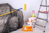 Buckets with paint, wrapped sofa and ladder on wall background. Conceptual photo of repairing works in  room  — Stock Photo