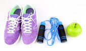 Sneakers and sport equipment. Conceptual photo of fitness progress. Isolated on white — Stock Photo