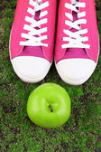 Beautiful gumshoes and apple on green grass background — Stock Photo