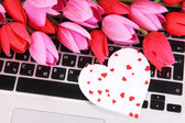 Bright heart and flowers on computer keyboard close up — Stock Photo