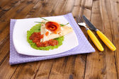 Pancake with salmon, red caviar and mayo, green onion, on plate, on color napkin, on wooden background — Stock Photo